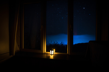 Photo for Night scene of stars seen through the window from dark room. Night sky inside dark room viewing from window with old vintage lantern. Long exposure shot - Royalty Free Image