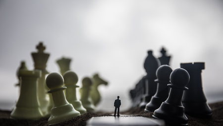 Foto de Chess concept of business and strategy ideas. Silhouette of a man standing in the middle of the road with giant chess figures. Little businessman on the road to success or troubles. Artwork decoration - Imagen libre de derechos