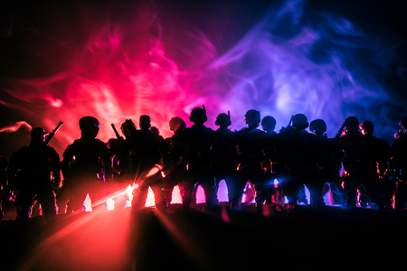 Photo pour Anti-riot police give signal to be ready. Government power concept. Police in action. Smoke on a dark background with lights. Blue red flashing sirens. Dictatorship power - image libre de droit