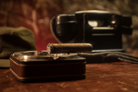 Foto de Close up of a Cuban cigar and ashtray on the wooden table. Communist dictator commander table in dark room. Army general`s work table concept. Artwork decoration - Imagen libre de derechos
