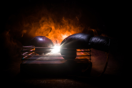 Photo pour Empty boxing ring with red ropes for match in the stadium arena. Boxing gloves ready to fight. Empty space for text. Foggy background with light. Selective focus - image libre de droit