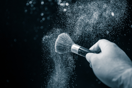 Photo pour Makeup brush in hand with cosmetic powder on dark background with light and smoke. Powder splash on dark. Selective focus - image libre de droit