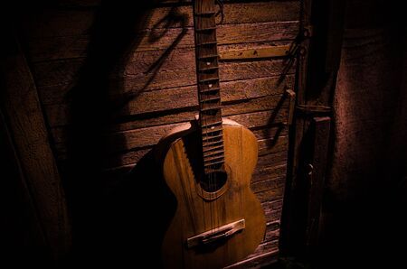 Photo pour An wooden acoustic guitar is against a grunge textured wall. The room is dark with a spotlight for your copyspace. old broken guitar - image libre de droit