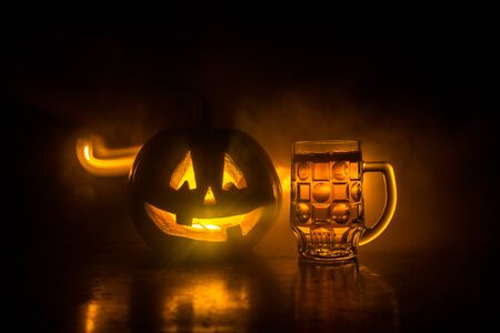 Photo pour Glass of cold light beer with pumpkin on a wooden table for Halloween. Glass of fresh beer and pumpkin on a dark toned foggy background - image libre de droit