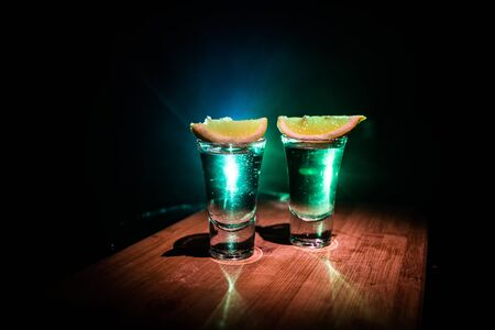 Photo for Club drink concept. Tasty alcohol drink cocktail tequila with lime and salt on vibrant dark background or glasses with tequila at a bar. Selective focus - Royalty Free Image