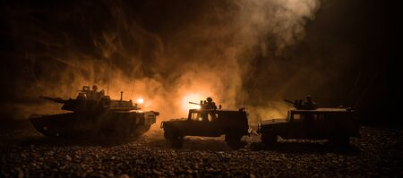 Foto de War Concept. Military silhouettes fighting scene on war foggy sky background at night. Armored vehicles with soldiers ready to attack. Artwork decoration. Selective focus - Imagen libre de derechos