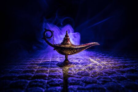 Photo pour Antique Aladdin arabian nights genie style oil lamp with soft light white smoke, Dark background. Lamp of wishes concept - image libre de droit