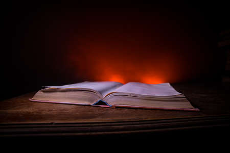 Photo for A stack of old books. Vintage book on wooden table. Magic lightning around a glowing book in the room of darkness. Selective focus - Royalty Free Image