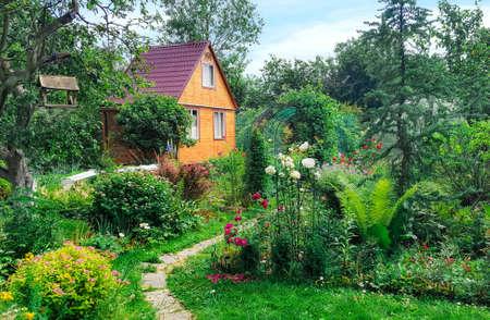 Foto de Summer wooden house on background of green garden,  landscape. - Imagen libre de derechos