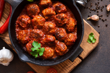 Photo pour Meatballs in sweet and sour tomato sauce on the kitchen table. Top view - image libre de droit