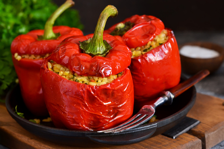Photo for Red pepper stuffed with meat, bulgur and vegetables in a cast-iron pan. Baked stuffed peppers. - Royalty Free Image