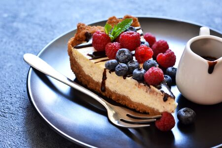Photo pour Homemade vanilla cheesecake with chocolate sauce and berries on a concrete background.   - image libre de droit