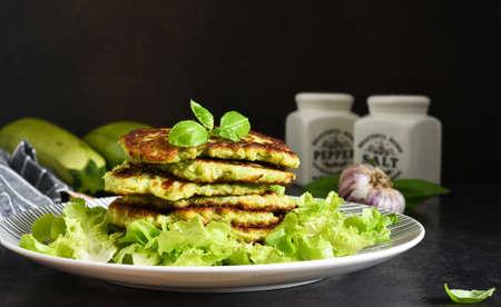 Foto für Zucchini pancakes with sauce and garlic on a concrete black background. - Lizenzfreies Bild
