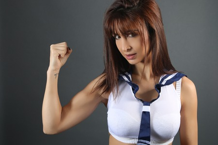 Young woman in schoolgirl costume showing her biceps