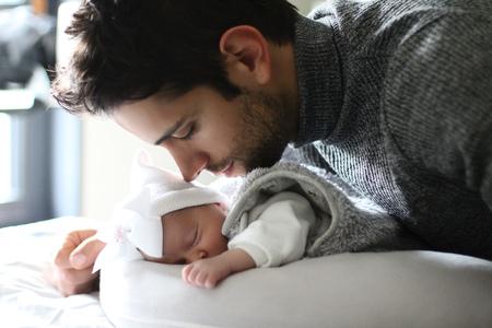 Foto de Proud father kissing his newborn baby daughter - Imagen libre de derechos