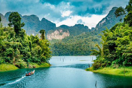 Mountain scenery with with tropical rain forest in the background and blue water lake in the foreground during a sunny day at Ratchaprapha Dam at Khao Sok National Park, Surat Thani Province, Thailand