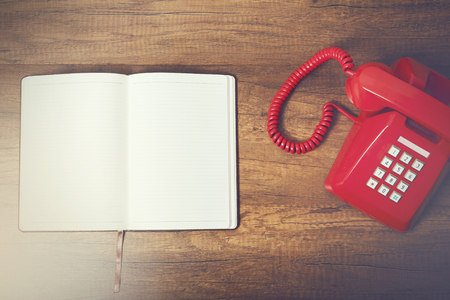 Notebook with retro red phone on wooden table, retro style concept