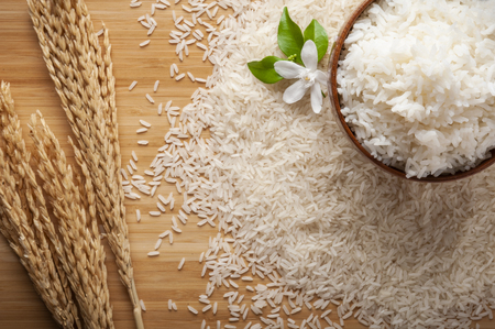 Foto de Top view of jasmine rice in a bowl on dark wooden table with rice plants, jasmine flower, ear of rices with jasmine rice in a bowl , rice scatter on the floor. - Imagen libre de derechos