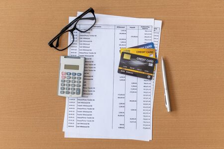 Photo pour Calculator and Pen on Bank statement and credit card on a Wooden table - image libre de droit