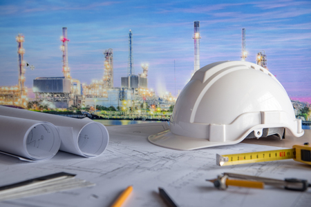 Foto de architectural drawing plan of refinery plant with blueprint rolls, protection safety helmet and project tools on work table, building construction industry concepts - Imagen libre de derechos