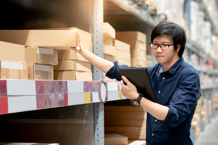 Photo pour Young Asian man doing stocktaking of product in cardboard box on shelves in warehouse by using digital tablet. physical inventory count concept - image libre de droit