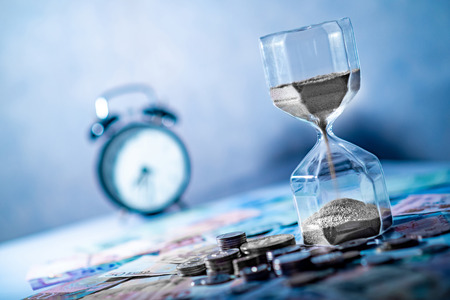 Photo pour Sand running through the shape of hourglass on table with banknotes and coins of international currency. Time investment and retirement saving. Urgency countdown timer for business deadline concept - image libre de droit