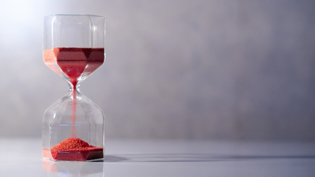 Photo pour Red sand running through the shape of modern hourglass on white table.Time passing and running out of time. Urgency countdown timer for business deadline concept with copy space - image libre de droit