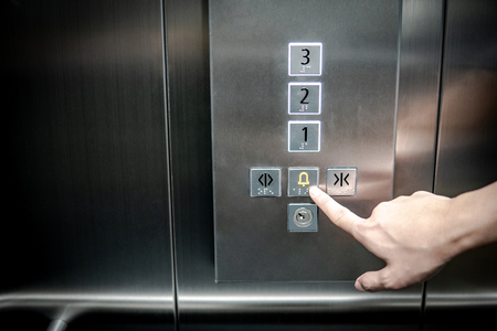 Foto de Male forefinger pressing on emergency stop and alarm button in elevator (lift). Mechanical engineering concept - Imagen libre de derechos