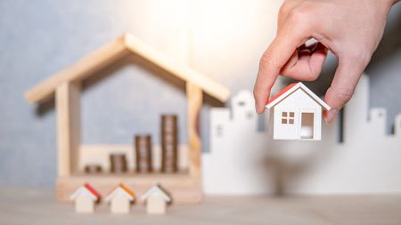 Photo pour Real estate or property investment growing business. Home mortgage loan rate. Saving money for retirement concept. Male hand holding house model with blurred coin stack in house frame on the table. - image libre de droit
