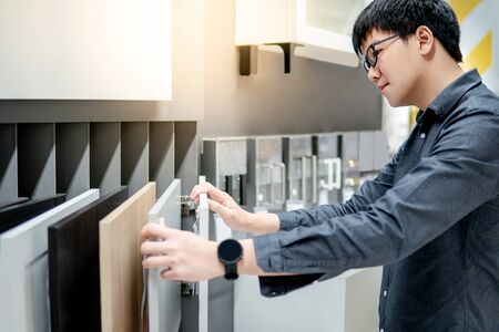 Photo for Asian man choosing cabinet panel materials or countertops for built-in furniture design. Shopping furniture and decoration. Home improvement concept - Royalty Free Image