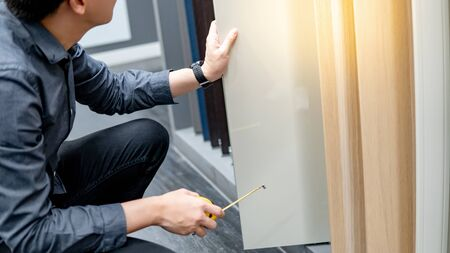 Photo for Asian man using tape measure on cabinet panel choosing materials or countertops for built-in furniture design. Shopping furniture and house decoration. Home improvement concept - Royalty Free Image