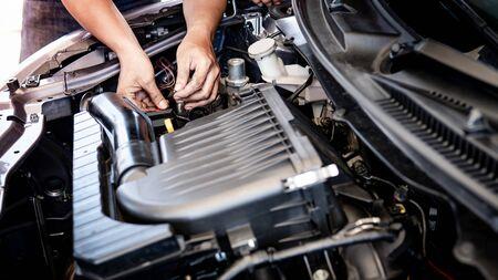 Photo pour Male hand of auto mechanic fixing car engine in the garage. Automobile industry concept - image libre de droit