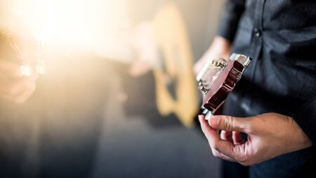 Photo for Male hand guitarist adjusting pegs on acoustic guitar during music lesson at home. String musical instrument concept - Royalty Free Image