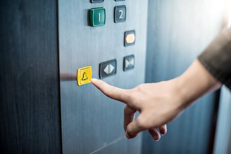 Photo pour Male forefinger pressing on emergency stop and alarm button in elevator (lift). Mechanical engineering concept - image libre de droit