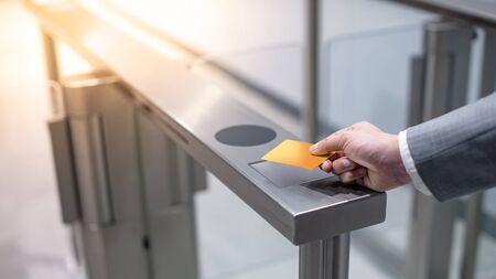 Foto de Businessman hand with business wear using orange smart card to open automatic gate machine in office building. Working routine concept - Imagen libre de derechos