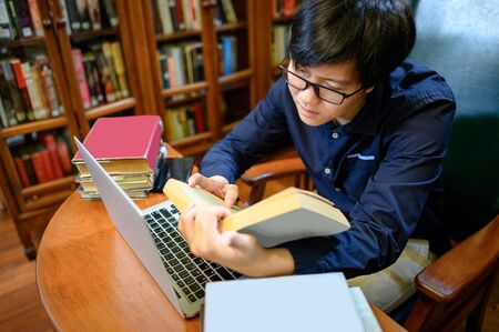 Photo pour Asian man university reading book and using laptop computer nearby vintage bookcase or bookshelf in college library. Textbook resources for education research. Scholarship opportunity concept - image libre de droit