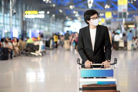 Photo pour Asian businessman wearing suit and face mask walking with airport trolley and suitcase luggage in airport terminal. Coronavirus (COVID-19) outbreak prevention. Health awareness for pandemic protection - image libre de droit