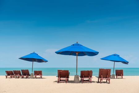 Photo for Group of wooden beach bench under parasol umbrella on tropical island beach. Holiday relaxation with turquoise sea and blue sky landscape. Summer vacation travel concept - Royalty Free Image
