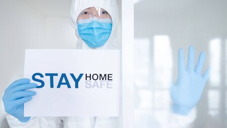 Photo pour Doctor or medical worker in personal protective equipment (PPE) suit, mask and gloves showing paper with message 'Stay home Stay safe'. Quarantine campaign during Coronavirus (COVID-19) pandemic. - image libre de droit