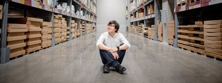 Foto für Asian shopper man sitting between cardboard box shelves aisle in warehouse choosing what to buy. Shopping lifestyle in department store. Buying or purchasing factory goods. Inventory industry concept - Lizenzfreies Bild