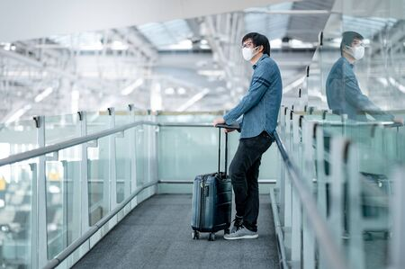 Photo pour Asian man tourist wearing face mask carrying suitcase luggage waiting in airport terminal gate hall. Coronavirus (COVID-19) pandemic prevention when travel. Health awareness and social distancing - image libre de droit