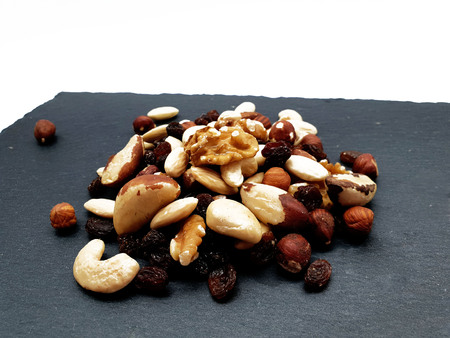 Trail mix isolated on white background on a slate plate