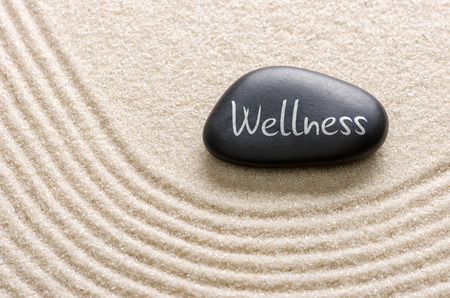A black stone with the inscription Wellness