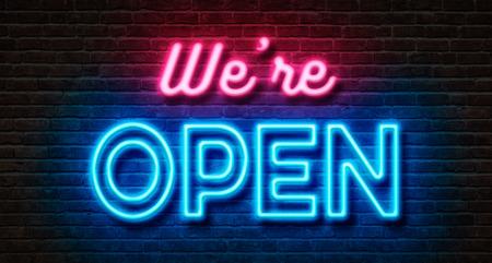 Foto de Neon sign on a brick wall - We are open - Imagen libre de derechos