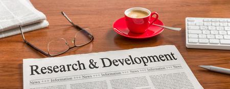 Photo pour A newspaper on a wooden desk - Research and Development - image libre de droit