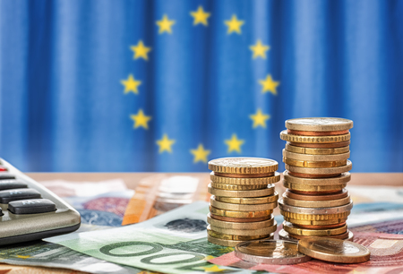 Photo pour Banknotes and coins in front of the flag of the European Union - image libre de droit