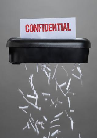 Foto de A shredder destroying a document - Confidential - Imagen libre de derechos