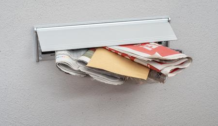 Foto de  Newspapers and a letter in a mail slot - Imagen libre de derechos