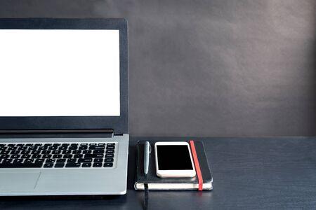 Foto de Laptop, smartphone, notebook, pen, on black wooden table with black background - Imagen libre de derechos