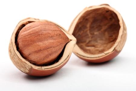 Close-up of hazelnut in cracked nutshell on the white background